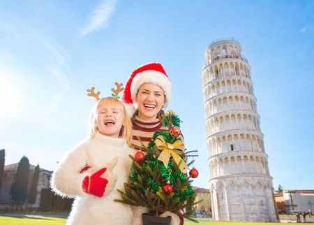 christmas spending: Mother in Christmas hat and daughter in funny reindeer antlers holding Christmas tree in front of Leaning Tour of Pisa, Italy and showing thumbs up. They spending exciting Christmas time traveling.