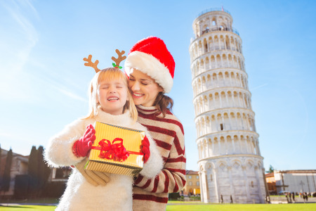 christmas spending: Happy mother in Christmas hat hugging daughter wearing funny reindeer antlers and holding gift box in front of Leaning Tour of Pisa, Italy. They spending exciting Christmas time traveling.