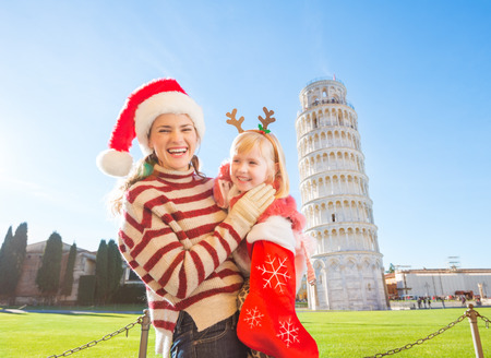 gift spending: Mother in Christmas hat holding daughter in funny reindeer antlers pulling out gift from Christmas sock. Leaning Tour of Pisa in background. They spending exciting Christmas time traveling Italy
