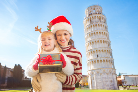 christmas spending: Portrait of happy mother in Christmas hat hugging daughter wearing funny reindeer antlers and holding gift box in front of Leaning Tour of Pisa, Italy. They spending exciting Christmas time traveling.