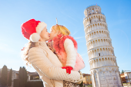 christmas spending: Mother in Christmas hat and daughter wearing funny reindeer antlers kissing in front of Leaning Tour of Pisa, Italy. They spending exciting Christmas time traveling.