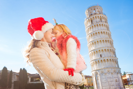 christmas spending: Touching moment of happy mother in Christmas hat and daughter wearing funny reindeer antlers standing in front of Leaning Tour of Pisa, Italy. They spending exciting Christmas time traveling. Stock Photo