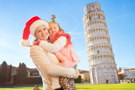 christmas spending: Happy mother in Christmas hat and daughter wearing funny reindeer antlers hugging in front of Leaning Tour of Pisa, Italy. They spending exciting Christmas time traveling.
