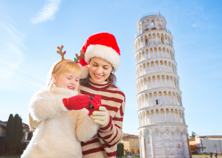christmas spending: Happy mother in Christmas hat and daughter wearing funny reindeer antlers checking photos on camera in front of Leaning Tour of Pisa, Italy. They spending exciting Christmas time traveling.