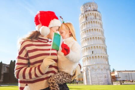 christmas spending: Happy mother in Christmas hat and daughter wearing funny reindeer antlers hugging behind Italian flag in front of Leaning Tour of Pisa, Italy. They spending exciting Christmas time traveling. Stock Photo