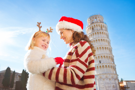 christmas spending: Smiling mother in Christmas hat and cosy sweater and daughter wearing funny reindeer antlers standing in front of Leaning Tour of Pisa, Italy. They spending exciting Christmas time traveling. Stock Photo