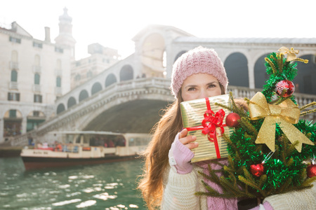 thrilling: Young woman in cosy knitted sweater with Christmas tree hiding behind gift box while standing in front of Rialto Bridge. Unique views of Venice, Italy making Christmas season even more thrilling.