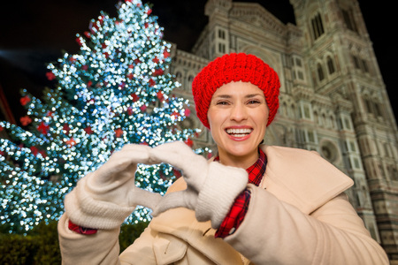 shaped hands: Happy young woman showing heart shaped hands in front of Christmas tree near Duomo in the evening. She having holiday tour and enjoying Christmas decorated historical area of Florence, Italy