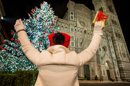 rejoicing: Woman in white coat with gift box rejoicing in front of Christmas tree near Duomo in the evening. She having holiday tour and enjoying Christmas decorated historical area of Florence, Italy
