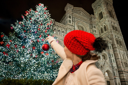 pretend: Woman pretend decorating Christmas tree near Duomo with Christmas ball. Evening. Christmas decorated historical area of Florence, Italy