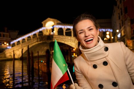 stunning: Portrait of happy elegant young woman showing Italian flag while standing in front of Rialto Bridge in the evening. She having Christmas time trip and enjoying stunning views of Venice, Italy