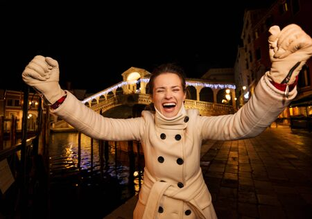 rejoicing: Happy elegant young woman in white coat rejoicing while standing in front of Rialto Bridge in the evening. She having Christmas time trip and enjoying stunning views of Venice, Italy