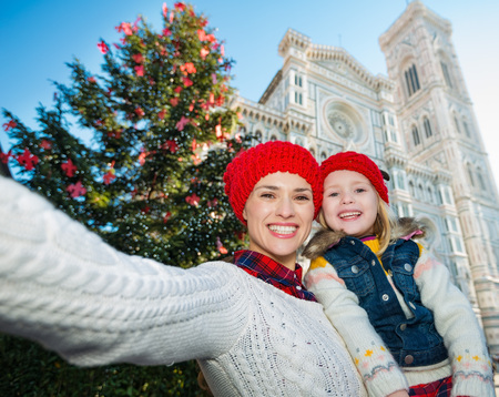 christmas church: Happy mother and daughter taking selfie in front of Christmas tree near Duomo in Florence, Italy. Modern family enjoying carousel of Christmas time events in heart of the Renaissance. Stock Photo