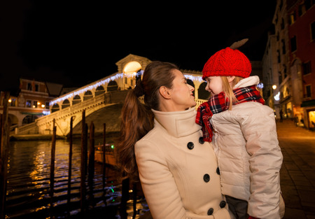 rialto: Modern family take the best of Christmas season by having a fascinating trip to Venice, Italy. Happy mother and daughter in the front of Rialto Bridge