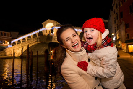 grand kids: Modern family take the best of Christmas season by having a fascinating trip to Venice, Italy. Portrait of laughing mother and daughter in the front of Rialto Bridge