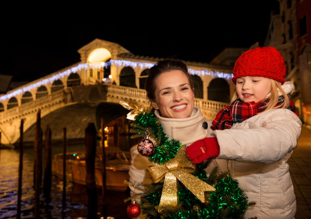 grand kid: Modern family take the best of Christmas season by having a fascinating trip to Venice, Italy. Happy mother and daughter with Christmas tree in the front of Rialto Bridge