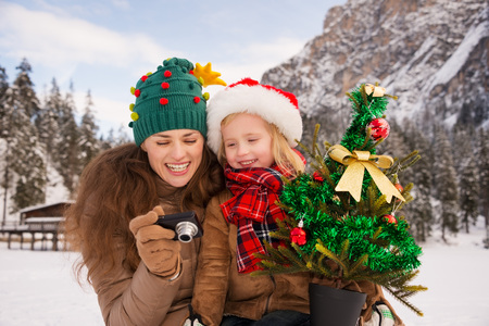 winter photos: Winter outdoors on Christmas can be fairytale-maker for a children or even an adults. Happy mother and child with Christmas tree checking photos in digital camera in the front of mountains