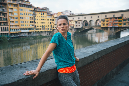staying: Young athletic woman is staying next to Arno riverside and thinking about distance for fitness jogging