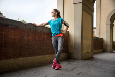 'getting ready': Young fitness woman is getting ready for outdoors jogging in Florence, Italy Stock Photo