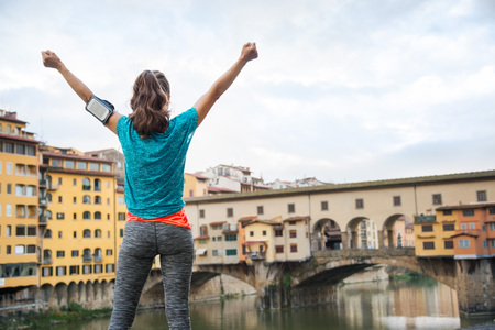 rejoicing: Fitness female in sporty outfit standing with hands up and rejoicing in front of Ponte Vecchio, Italy Stock Photo