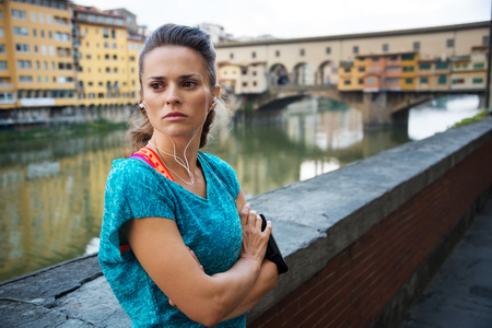 staying: Young сoncentrated woman in sportswear is staying next to Ponte Vecchio bridge with mp3 player and getting ready for outdoor fitness Stock Photo