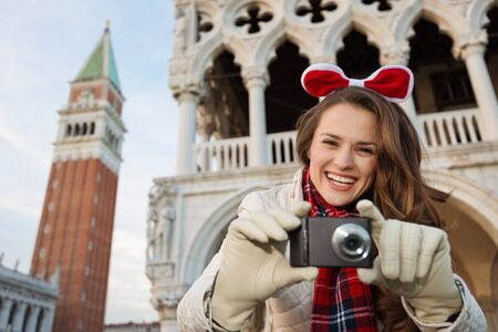christmas spending: Christmas season brings spirit of travel. Portraits of smiling young woman tourist with digital photo camera. She is spending Christmas holidays in Venice, Italy - the unique city of water