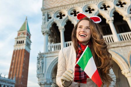 christmas spending: Christmas season brings spirit of travel. Portrait of smiling young woman tourist with Italian flag. She is spending Christmas holidays in Venice, Italy - the unique city of water