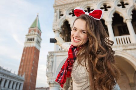 Christmas season brings spirit of travel. Smiling young woman tourist taking photos while spending Christmas holidays in Venice, Italy - the unique city of water Stock fotó