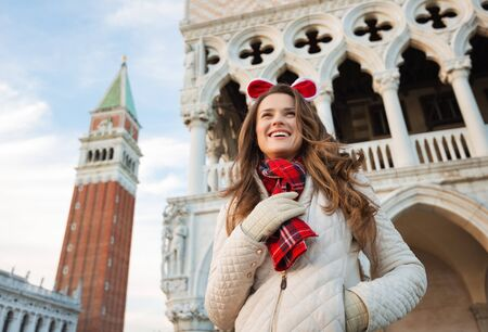 christmas spending: Christmas season brings spirit of travel. Smiling young woman tourist is looking into distance. She is spending Christmas holidays in Venice, Italy - the unique city of water Stock Photo
