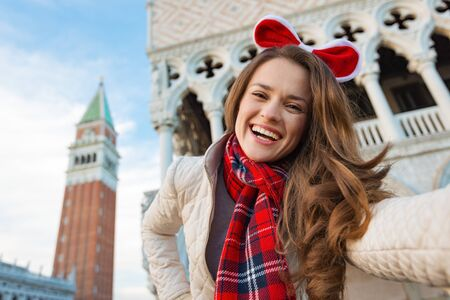 campanile: Christmas season brings spirit of travel. Smiling young woman tourist taking selfie while spending Christmas holidays in Venice, Italy - the unique city of water