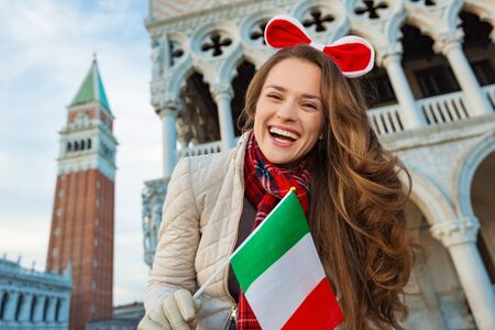 christmas spending: Christmas season brings spirit of travel. Smiling young woman tourist showing Italian flag. She is spending Christmas holidays in Venice, Italy - the unique city of water