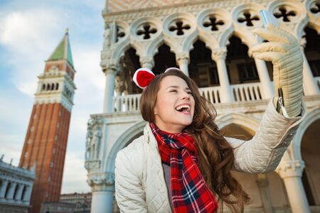 christmas spending: Christmas season brings spirit of travel. Smiling young woman tourist taking selfie while spending Christmas holidays in Venice, Italy - the unique city of water
