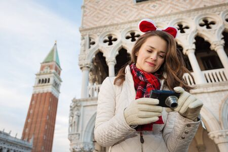 christmas spending: Christmas season brings spirit of travel. Young woman tourist checking photos in camera. She is spending Christmas holidays in Venice, Italy - the unique city of water