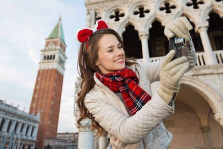 campanile: Christmas season brings spirit of travel. Smiling young woman tourist taking photos while spending Christmas holidays in Venice, Italy - the unique city of water