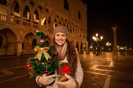 anticipated: Dress up. Plan hit list. It is time to land in thrilling Venice, Italy on the years most anticipated season - Christmas. Smiling woman with Christmas tree and gift box standing on Piazza San Marco Stock Photo