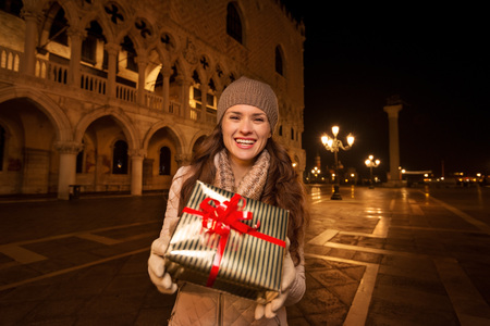 anticipated: Dress up. Plan hit list. It is time to land in thrilling Venice, Italy on the years most anticipated season - Christmas. Happy woman showing Christmas gift box while standing on Piazza San Marco
