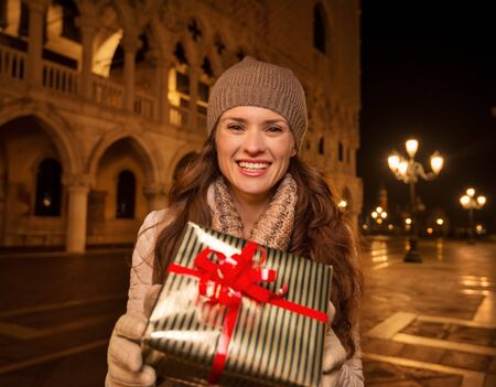 anticipated: Dress up. Plan hit list. It is time to land in thrilling Venice, Italy on the years most anticipated season - Christmas. Smiling woman showing Christmas gift box while standing on Piazza San Marco