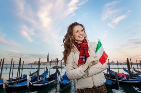 irresistible: Sunset brings to life irresistible magic of Venice the unique Italian city. Young woman traveler with Italian flag standing on embankment in the front of the line of gondolas and looking into distance