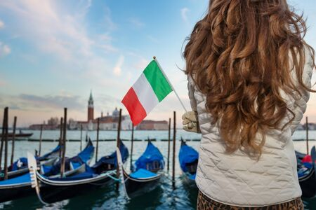 irresistible: Sunset brings to life irresistible magic of Venice - the unique Italian city. Closeup on Italian flag in hands of woman traveler standing on embankment in the front of the line of gondolas