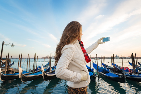 anonym: Sunset brings to life irresistible magic of Venice - the unique Italian city. Young woman traveler standing on embankment in the front of the line of gondolas taking photos Stock Photo