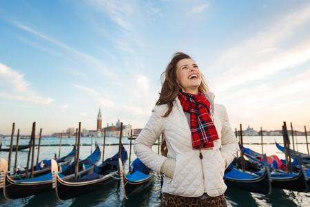 irresistible: Sunset brings to life irresistible magic of Venice - the unique Italian city. Happy young woman traveler standing on embankment in the front of the line of gondolas Stock Photo