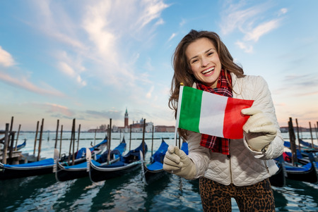 irresistible: Sunset brings to life irresistible magic of Venice - the unique Italian city. Young woman traveler showing Italian flag while standing on embankment in the front of the line of gondolas