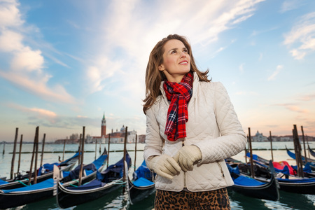 irresistible: Sunset brings to life irresistible magic of Venice - the unique Italian city. Dreamy young woman traveler standing on embankment in the front of the line of gondolas and looking into distance Stock Photo
