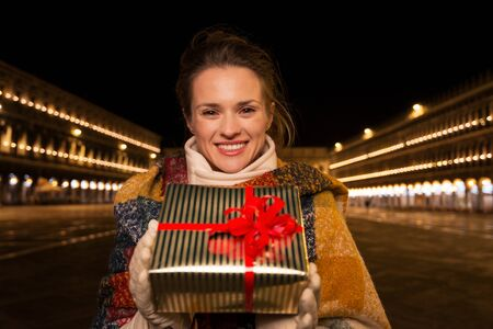 allure: Excitement of Christmas time and allure of long-time favourite Venice, Italy. Portrait of happy woman holding Christmas gift box while standing on Piazza San Marco in the evening