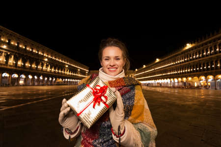 campanile: Excitement of Christmas time and allure of long-time favourite Venice, Italy. Portrait of smiling woman holding Christmas gift box while standing on Piazza San Marco in the evening