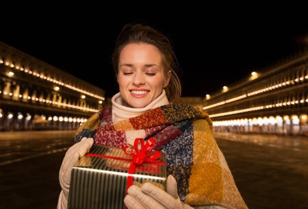 campanile: Excitement of Christmas time and allure of long-time favourite Venice, Italy. Portrait of smiling woman looking on Christmas gift box while standing on Piazza San Marco in the evening Stock Photo