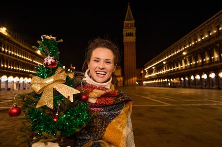 allure: Excitement of Christmas time and allure of long-time favourite Venice, Italy. Smiling woman holding Christmas tree while standing on Piazza San Marco in the evening Stock Photo