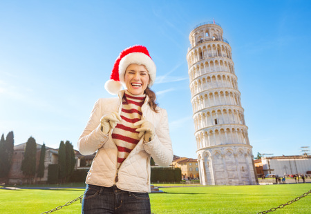 going for it: Young, itching from energy and searching for excitement. Im going to Christmas trip to Italy. It is a no-brainer. Portrait of smiling woman in Santa hat in front of Leaning Tour of Pisa.