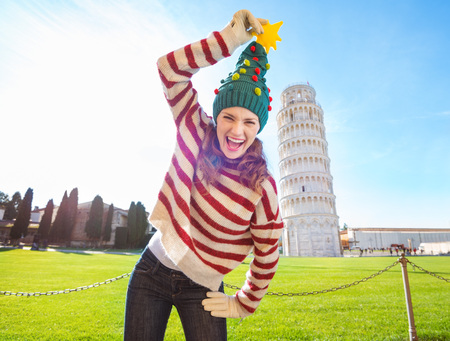 going for it: Young, itching from energy and searching for excitement. Im going to Christmas trip to Italy. It is a no-brainer. Smiling woman make fun of Christmas tree hat in front of Leaning Tour of Pisa Stock Photo