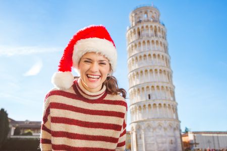 going for it: Young, itching from energy and searching for excitement. Im going to Christmas trip to Italy. It is a no-brainer. Portrait of happy woman in Santa hat in front of Leaning Tour of Pisa. Stock Photo